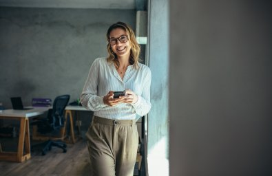 Cheerful woman standing in office with her phone. Businesswoman with cell phone in hand looking at camera and smiling.