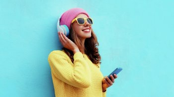 Fashion pretty sweet carefree girl listening to music in headphones with smartphone wearing a colorful pink hat yellow sunglasses sweater over blue background