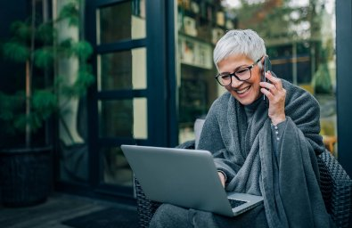 Smiling elder woman using laptop and talking on mobile phone, portrait.