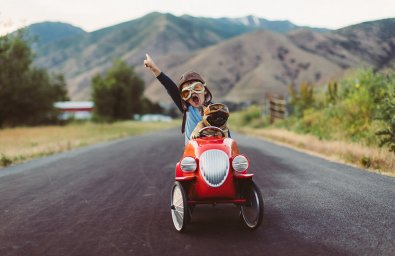 A young boy with flying goggles and flight cap races a red toy car with his pet and best friend French Bulldog along a small road in Utah, USA. Sometimes a road trip journey with your best friend and some fresh air in your face is the best medicine for the soul.