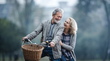 Happy mature couple communicating while riding on a bike in the park. Copy space.